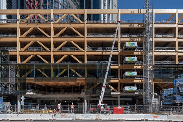 A building constructed from around 1750 pieces of timber has reached its top floor, marking structural completion for the project in Baranagroo, Sydney.